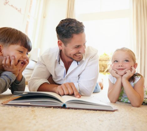 Father with two kids reading a story book.