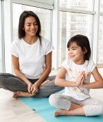 Happy people woman and little kid practicing yoga indoor, sittin
